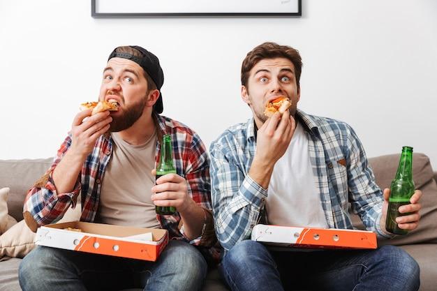 Foto van twee mannelijke mannen in casual shirts die pizza eten en bier drinken, terwijl ze thuis naar een voetbalwedstrijd kijken