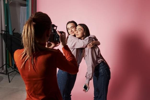 Foto van twee meisjes die elkaar omhelzen en worden gefotografeerd door een vrouwelijke cameraman in de studio
