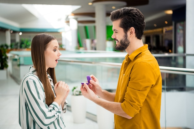 Foto van twee mensen aantrekkelijke dame knappe kerel paar bezoek winkelcentrum vriendje doe voorstel met me trouwen onverwachte opwinding draag casual jeans shirt outfit binnenshuis
