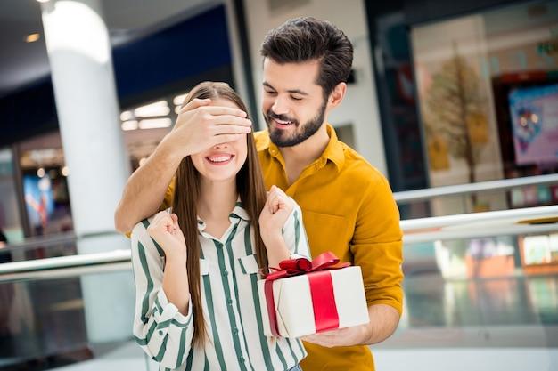 Foto van twee mensen aantrekkelijke dame knappe kerel paar onverwachte ogen dicht voorbereid verrassing geschenkdoos verjaardag datum bezoek winkelcentrum draag casual jeans shirt outfit binnenshuis