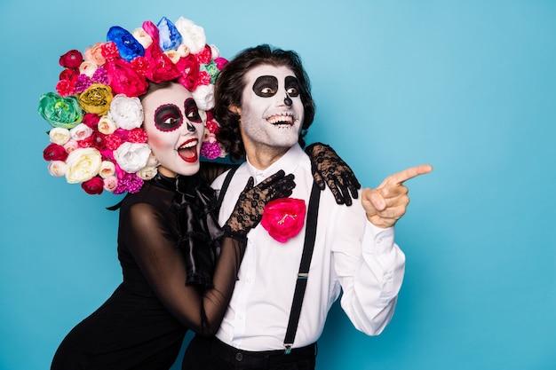 Foto van twee mensen zombie eng man dame knuffelen direct vinger kijken lege ruimte opgewonden buren decor dragen zwarte jurk dood kostuum rozen hoofdband bretels geïsoleerde blauwe kleur achtergrond