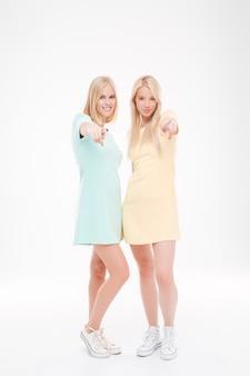 Foto van twee mooie dames die naar voren wijzen. staande over witte muur.