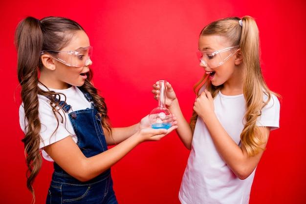 Foto van twee mooie kleine dames ijverige schoolkinderen maken chemisch experiment opgewonden resultaten houden buis dragen jeans overall wit t-shirt geïsoleerde rode kleur achtergrond
