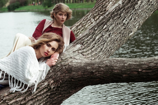 Foto van twee mooie vrouwen die op een boom dichtbij meer stellen.