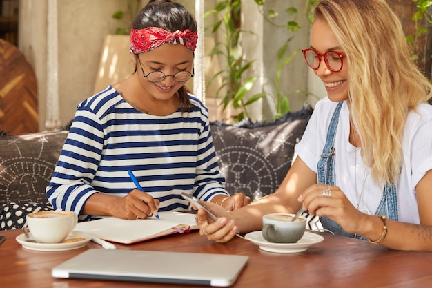 Foto van twee multi-etnische vrouwen zitten samen bij coffeeshop