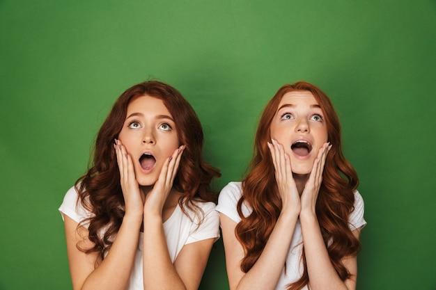 Foto van twee roodharige vrouwen 20s in witte t-shirts die wangen aanraken met open mond en naar boven kijken, geïsoleerd op groene achtergrond