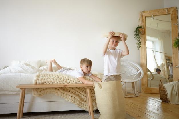 Foto van twee schattige blanke schooljongens die plezier hebben binnenshuis, samen actieve spelletjes spelen in de slaapkamer van de ouders, zich gelukkig en zorgeloos voelen. leuke mannelijke kinderen die zich thuis vermaken