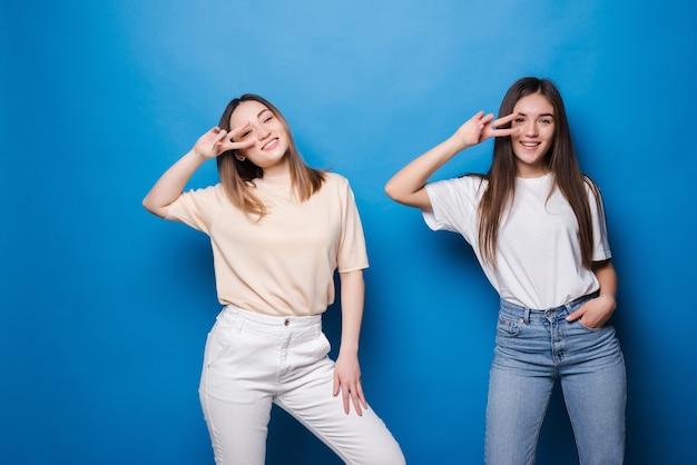 Foto van twee speelse meisjes die samen staan en vredesgebaren tonen over blauwe muur