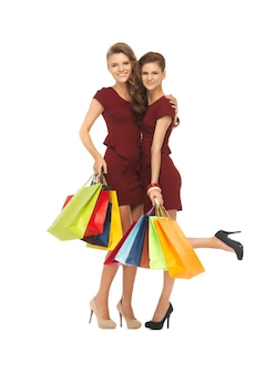 Foto van twee tienermeisjes in rode jurken met boodschappentassen