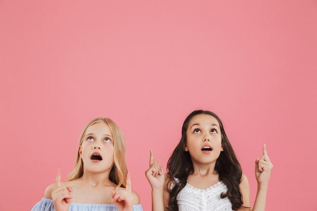 Foto van twee verrast of geschokt meisjes 8-10 jaar oud in jurken op zoek naar boven met open mond en wijzende vingers naar copyspace.