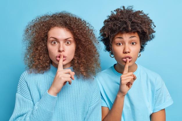 Foto van twee verraste vrouwen van gemengd ras maken stiltegebaar en vragen om geheim te houden, tenzij taboe-gebaar zegt stilte, ga naast elkaar staan tegen de blauwe muur. geheimhouding.