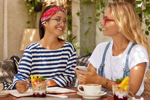 Foto van twee vriendelijke vrouwen schrijven gelukkige momenten over hun vakantie op een exotische plek in notitieboekje