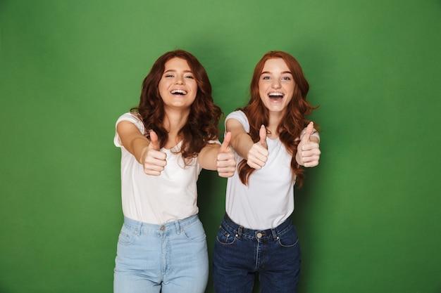 Foto van twee vrolijke roodharige vrouwen 20s in vrijetijdskleding lachend naar de camera en duimen opdagen, geïsoleerd op groene achtergrond
