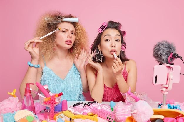 Foto van twee vrouwelijke schoonheidsbloggers die cosmetische beoordelingsvideo opnemen voor blog poeder en lippenstift aanbrengen, voorbereiden op date, krullend kapsel dragen, modieuze jurken, poseren binnenshuis. live uitzenden