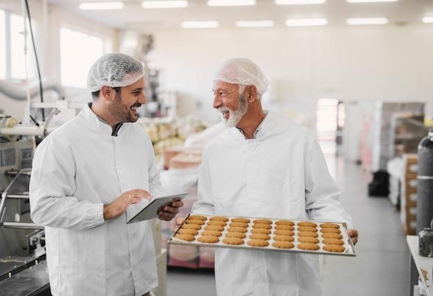 Foto van twee werknemers in steriele kleren in voedselfabriek die glimlachen en praten. oudere man houdt dienblad vol verse koekjes terwijl de jongere tablet vasthoudt en de productielijn controleert.