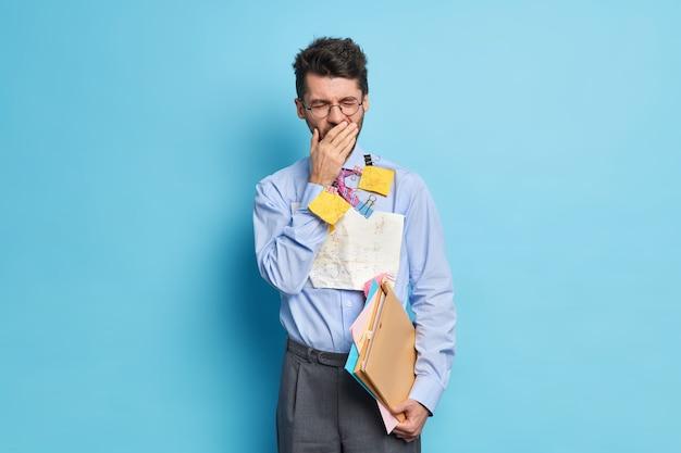 Foto van uitgeputte man gaapt na lange uren werken bereidt financieel verslag voor, draagt formele kleding vormt binnen