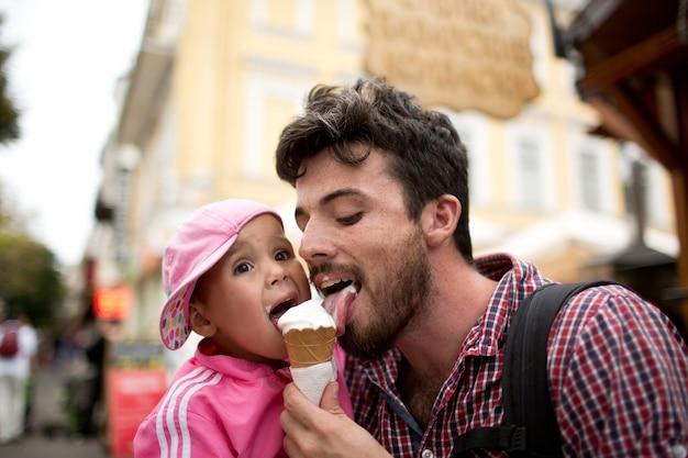 Foto van vader die van wit roomijs met dochter houdt. wandelen op straat en samen plezier hebben. lekker zoet ijs. samen tijd doorbrengen.