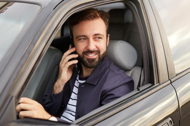 Foto van van jonge aantrekkelijke succesvolle bebaarde man in een blauw jasje en gestreept t-shirt, zit achter het stuur van de auto en wacht op een reactie op de telefoon.