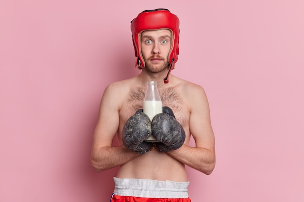 Foto van vastberaden mannelijke bokser heeft als doel het spel te winnen, bereidt zich voor op gevecht draagt bokshandschoenen en beschermende helm drinkt melk als bron van calcium zonder shirt.