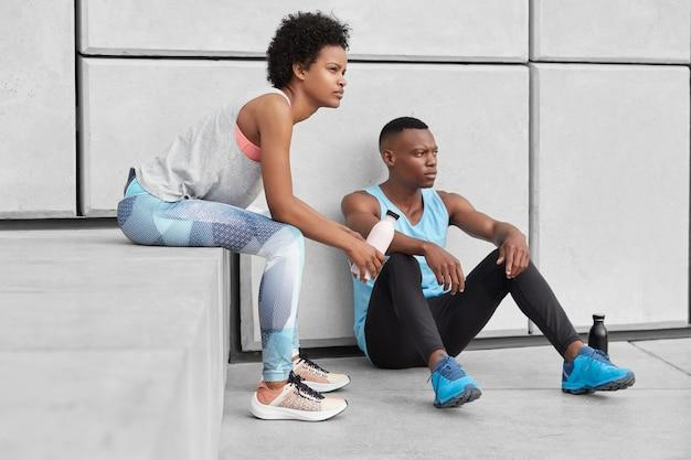 Foto van vastberaden vrouw en man met donkere huid, gezond lichaam, peinzende contemplatieve gezichtsuitdrukkingen, ontspannen afro-amerikaans meisje zit op trappen in de buurt van vriendje, moe na het spelen van basketbal