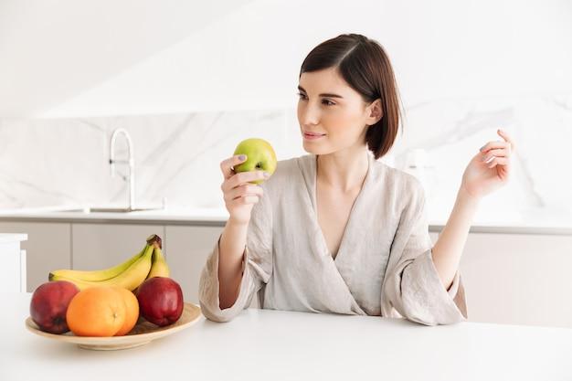 Foto van vegetarische jonge vrouw die thuis ontbijt in keuken heeft, en rijpe sappige vruchten eet