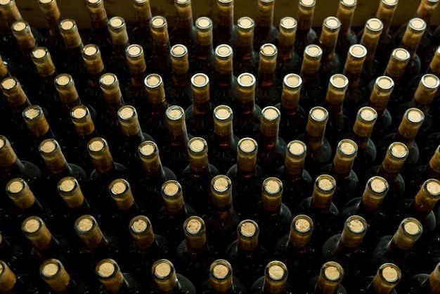 Foto van vele flessen met wijn in ondergronds, wijnmakerijconcept