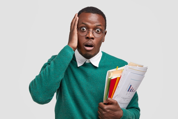 Foto van verbaasd donkere huid afro-amerikaanse man houdt statistische documenten, raakt hand op hoofd, staart naar camera met schok