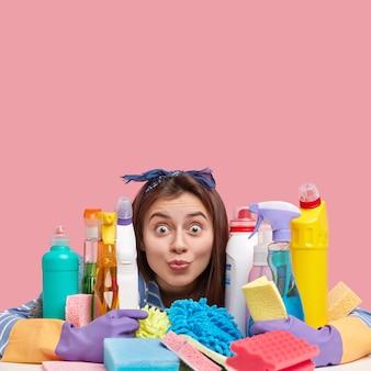 Foto van verbaasd donkerharige jonge vrouw met afgeluisterde ogen, heeft verbaasd kijken, maakt gebruik van schoonmaakmiddelen