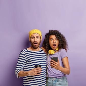 Foto van verbaasd gemengd ras paar kijken met omg-uitdrukkingen, vreselijk nieuws ontvangen, afro-vrouw houdt smartphoneapparaat vast, leest artikel online