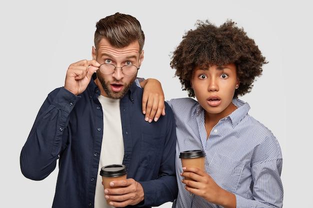 Foto van verbaasd gemengd ras vrouw en man staren met verbaasde uitdrukkingen