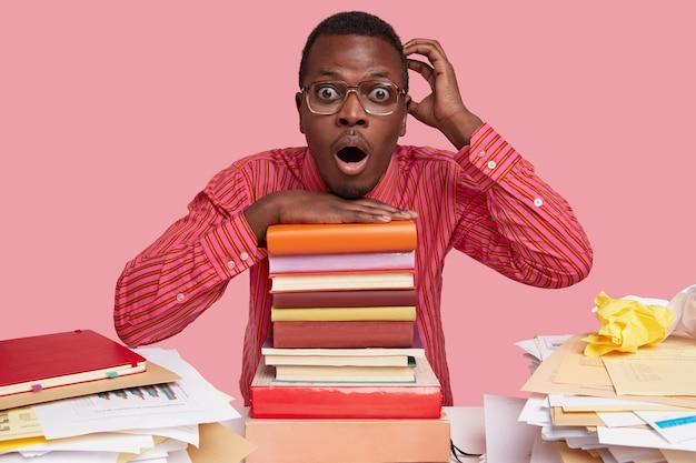 Foto van verbaasd geschokt zwarte afro-amerikaanse wonk krabt hoofd, heeft verbaasde blik, leunt op enorme stapel schoolboeken, heeft een ongemakkelijke blik