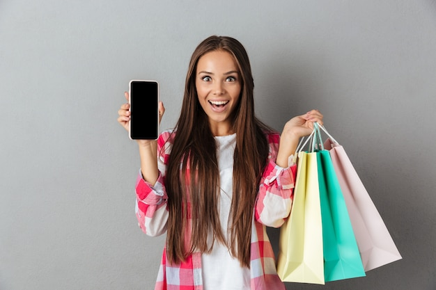 Foto van verbaasd jonge brunette bedrijf boodschappentassen, met blanco mobiel scherm