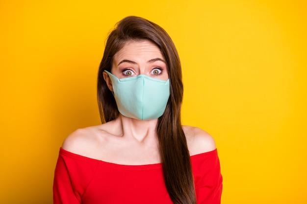Foto van verbaasd meisje met medisch masker hoor covid ncov quarantaine-informatie staren dragen rode, goed uitziende kleding geïsoleerd over heldere glanskleurachtergrond