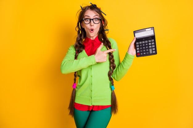 Foto van verbaasd meisje met rommelig kapsel punt vinger rekenmachine geïsoleerd op felle kleur achtergrond