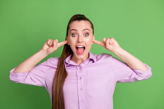 Foto van verbaasd meisje sluit dekking oren wijsvinger schreeuwen onder de indruk draag violette outfit geïsoleerd over groene kleur achtergrond