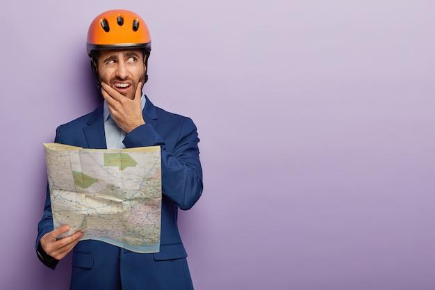 Foto van verbaasd ontevreden mannelijke ingenieur werknemer houdt kin, blauwdruk, bouw site kaart houdt, werkt op de bouwplaats, draagt harde hoed en blauwe pak