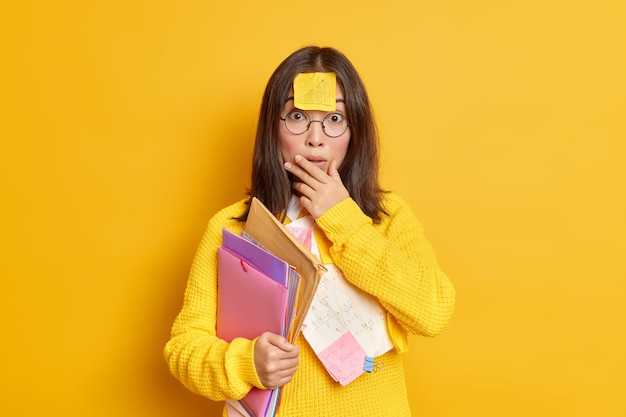 Foto van verbaasd verrast aziatische vrouwelijke student heeft memo notitie geplakt op voorhoofd bereidt cursussen draagt mappen met papieren maakt onderwijsproject werkt op haar opdracht studies op afstand