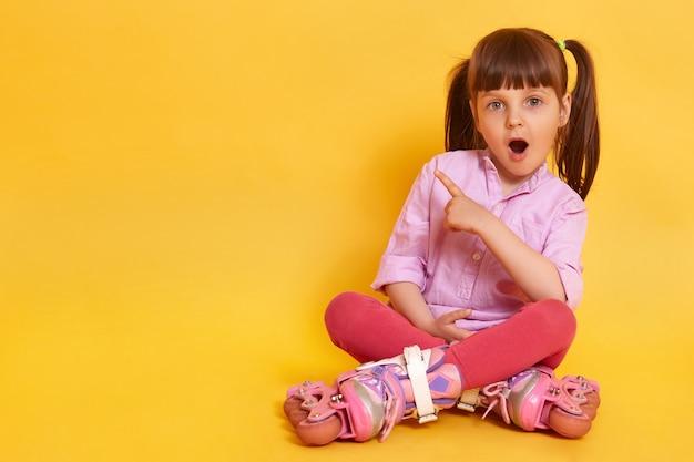 Foto van verbaasd vrouwelijk kind met wijd geopende mond zittend op de vloer
