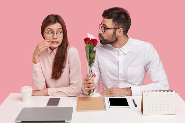 Foto van verbaasde aantrekkelijke vrouw klemt tanden, kijkt verlegen naar knappe man die haar boeket rozen geeft