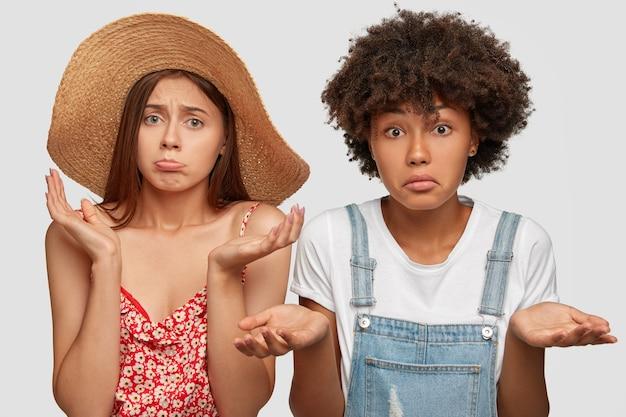 Foto van verbaasde aarzelende vrouwen van gemengd ras kijken met clueless uitdrukkingen