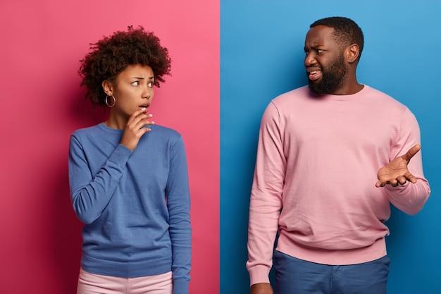Foto van verbaasde afro-amerikaanse vrouw en man hebben ontevreden uitdrukkingen, bespreken iets onaangenaams, kregen slecht nieuws
