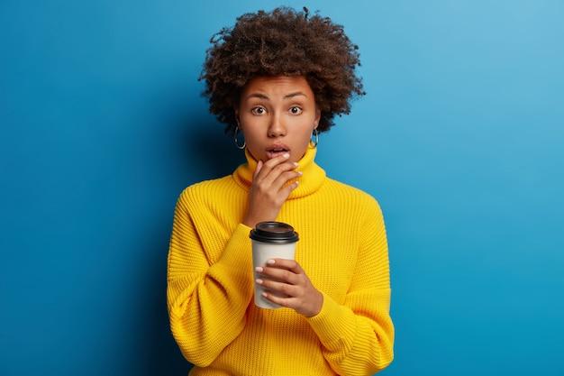 Foto van verbaasde bang donkere jonge vrouw houdt kin, poses met afhaalkoffie geïsoleerd over blauwe muur