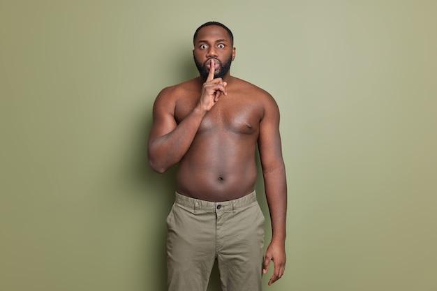 Foto van verbaasde bebaarde man maakt zwijgzaam gebaar zegt stilte zwijgen houdt wijsvinger op lippen