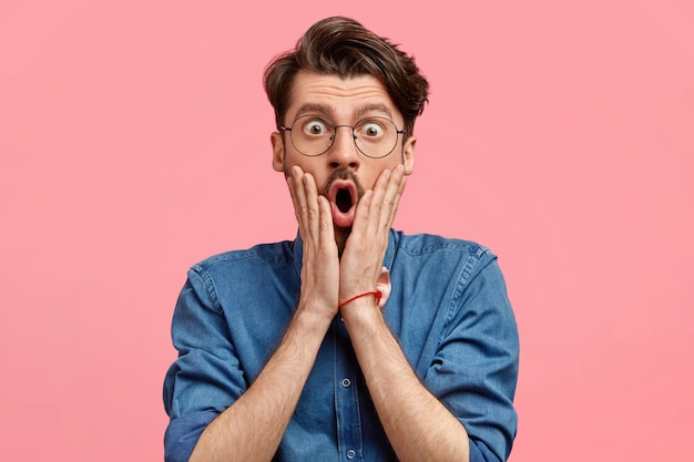 Foto van verbaasde bebaarde man met stijlvol kapsel houdt de handen op beide wangen, ziet er verrassend en geschokt uit, opent zijn mond wijd, gekleed in spijkerblouse, poseert tegen roze muur