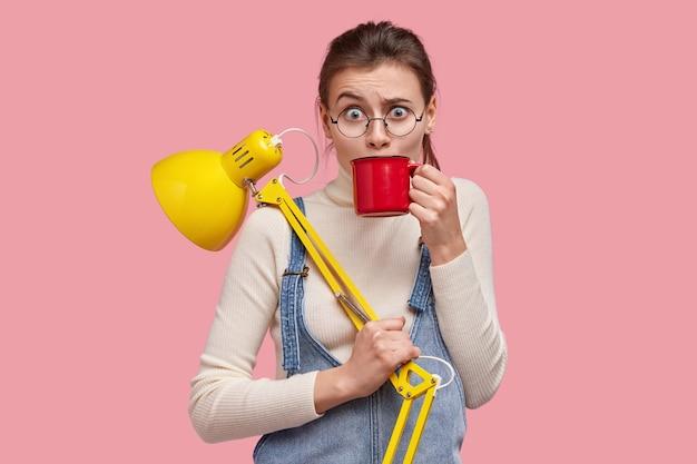 Foto van verbaasde blanke vrouw trekt wenkbrauwen op, drinkt drank uit rode mok, heeft pauze na het studeren, draagt tafellamp