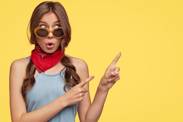 Foto van verbaasde brunette hipster heeft verbaasde uitdrukking, geeft aan met wijsvingers in de rechterbovenhoek