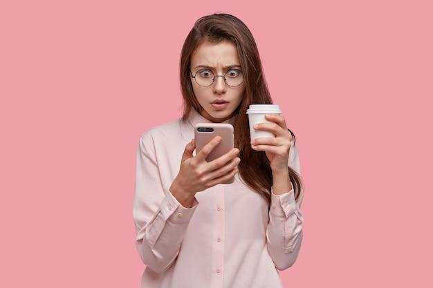Foto van verbaasde donkere vrouw kijkt met verbijsterde uitdrukking op het scherm van de mobiele telefoon, heeft een probleem, ontving onaangenaam nieuws