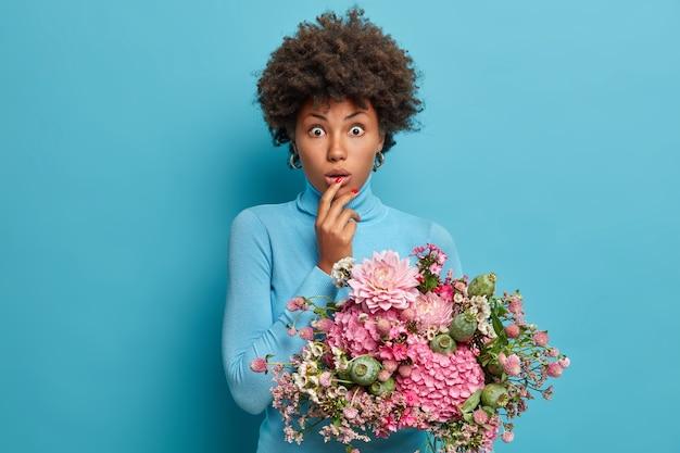 Foto van verbaasde donkere vrouw krijgt bloemen