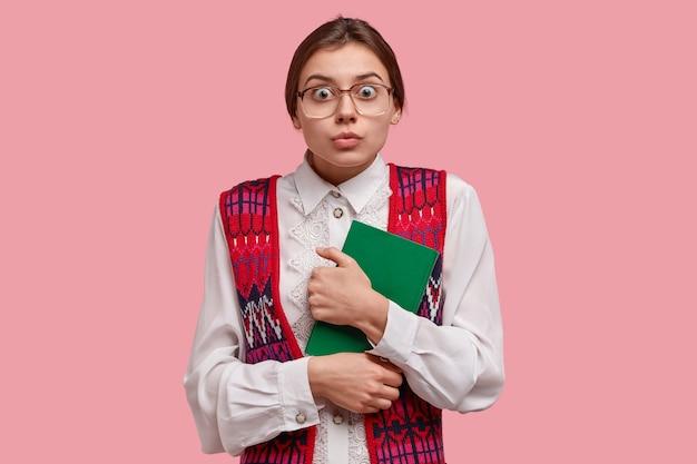 Foto van verbaasde europese vrouwelijke nerd staart door bril, draagt witte formele blouse en vest, draagt groene blocnote nauw, geschokt veel mensen komen op sollicitatiegesprek, zorgen voor praten