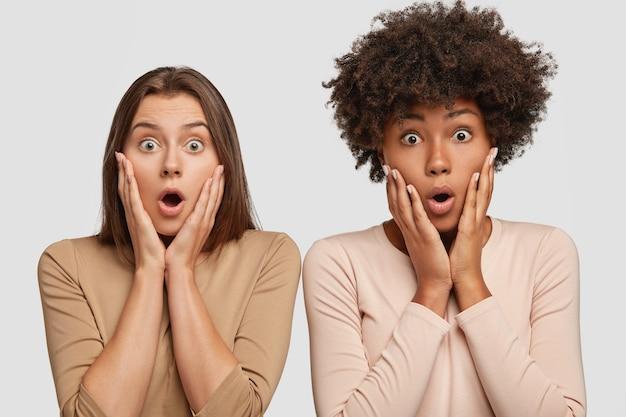 Foto van verbaasde interraciaal vriendelijke vriendinnen houden beide handen op het gezicht, snakken naar adem van verwondering, staan dicht bij elkaar